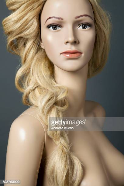 Nude, young female mannequin with a long, wavy, blond human hair wig in a loose french braid over her shoulder and pale skin, portrait.