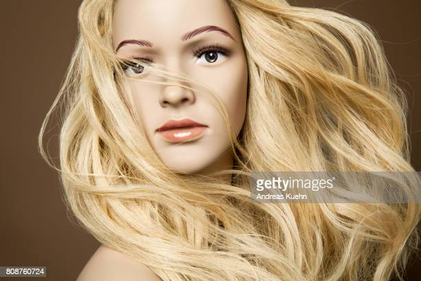 Nude young female mannequin with a long, wavy, blond human hair wig, pale skin and hair blowing across her face, cropped.