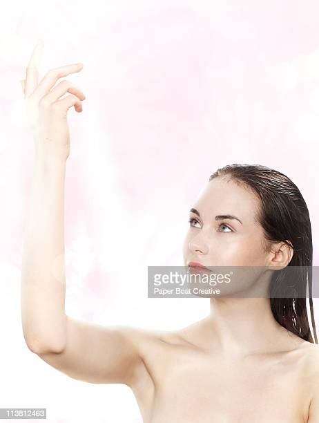 Nude young lady with her hand up