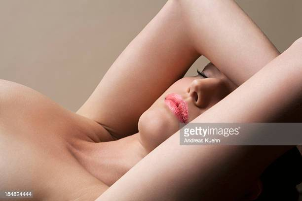 nude young woman laying back with eys closed. - セミヌード ストックフォトと画像