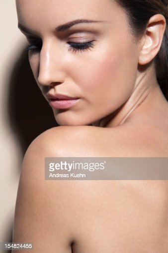 Nude Young Woman With Chin On Shoulder High-Res Stock