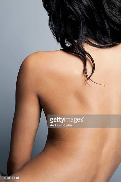 Nude young woman with her back towards camera.