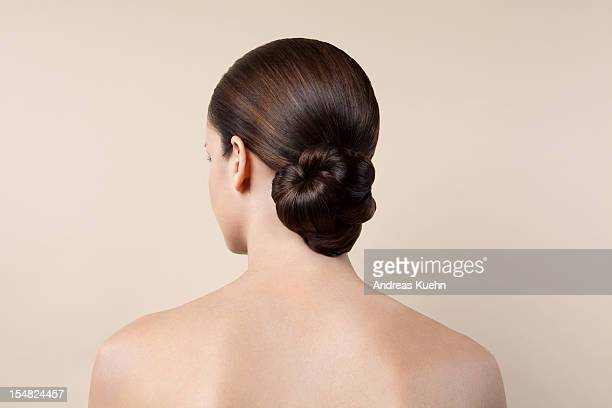 Nude young woman with up do, back view.