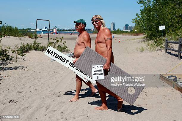 TORONTO ON AUGUST 22 Nudist David Fleming and Gene Dare carry signage at Hanlan's Point Beach August 22 2015 The men spend summer weekends at the...