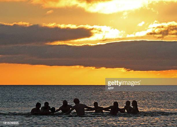 Nudists take part in the annual North East Skinny Dip as the sun rises at Druridge Bay in Northumberland northeast England on September 22 2013...