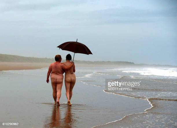 Nudists take part in the annual North East Skinny Dip at sunrise at Druridge Bay near Ashington Northumberland northeast England on September 25 2016...