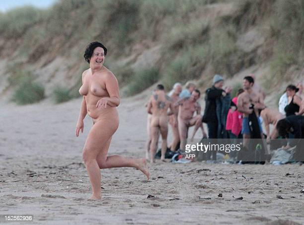 Nudists take part in the North East Skinny Dip at Druridge Bay in Northumberland at sunrise on September 22 2012 Over 200 bathers braved the cold in...