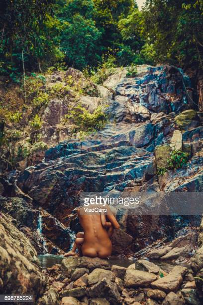 nudust woman with baby boy at waterfall - family naturist stock pictures, royalty-free photos & images