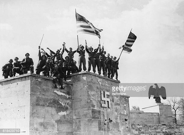 5/1945 Nuermberg Germany Men of the 45th Division US 7th army wave their American Flags from the very dias from which Hitler Goebbels Goering and...