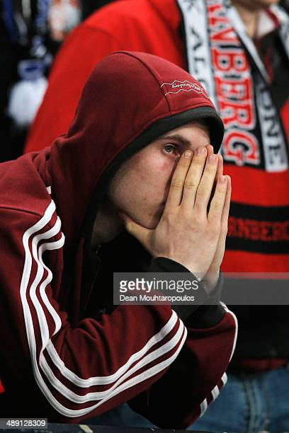 Nuernberg fan looks dejected with confirmed relegation after the Bundesliga match between FC Schalke 04 and 1 FC Nuernberg held at VeltinsArena on...