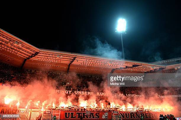 Nuernberg fans burn flares during the Bundesliga match between 1 FC Nuernberg and VfB Stuttgart at Grundig Stadium on March 26 2014 in Nuremberg...