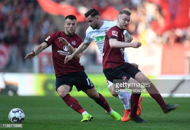 Nuernberg's German-Russian midfielder Eduard Loewen, Augsburg's German midfielder Marco Richter and Nuernberg's German midfielder Sebastian Kerk vie...