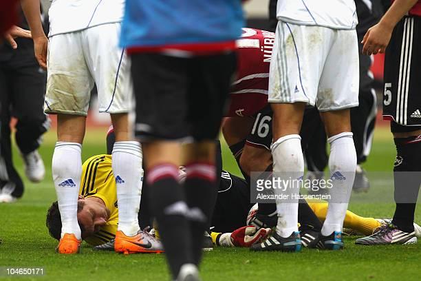 Nuernberg's keeper Raphael Schaefer gets injured after attacked by Jermaine Jones of Schalke during the Bundesliga match between 1 FC Nuernberg and...