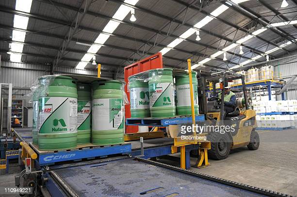 A Nufarm Ltd forklift operator lifts containers of liquid herbicide on to a conveyor belt for wrapping prior to distribution at the company's...