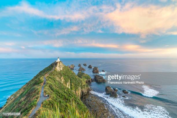 nugget point lighthouse, new zealand. - international landmark stock pictures, royalty-free photos & images