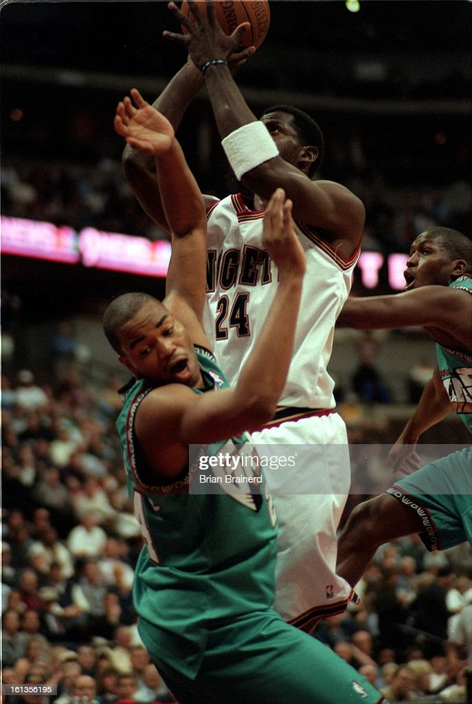 Nuggets Antonio McDyess draws an offensive foul as Grizzlies Othella Harrington goes to the ground Monday night at Pepsi Center. : News Photo