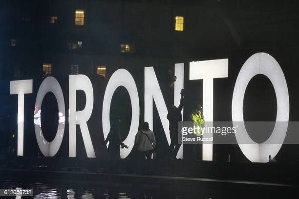 TORONTO ON OCTOBER 2 Nuit Blanche workers and security use nail polish remover to remove tags and graffiti from the iconic Toronto sign Nathan...