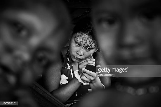 Nukak girl paints ornaments on her face with the red dye in a refugee settlement close to San Jose del Guaviare on September 04 2009 in San Jose del...