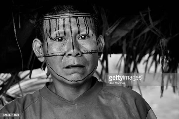 Nukak woman having her face decorated with the red dye painted ornaments stands in her shack in a refugee settlement close to San Jose del Guaviare...