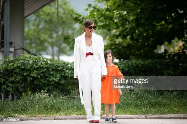 Nuki Chabukiani of Dots and Materiel wears a Materiel by Aleksandre Akhalkatsishvili white suit and outfit with her daughter who wears an orange...