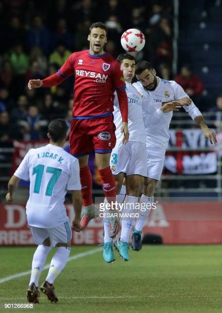 Numancia's defender Pere Milla vies with Real Madrid's Spanish defender Jesus Vallejo and Real Madrid's Spanish defender Dani Carvajal during the...