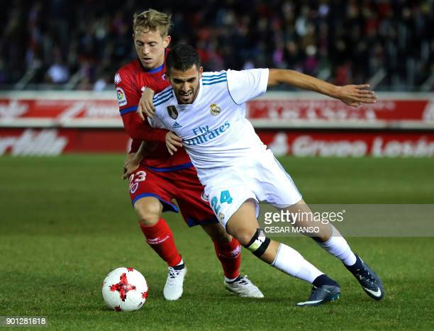 Numancia's midfielder Dani Nieto vies with Real Madrid's Spanish midfielder Daniel Ceballos during the Spanish Copa del Rey round of 16 first leg...