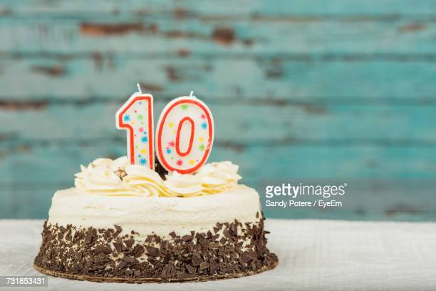 Number 10 Candle On Birthday Cake Over Table Against Wall