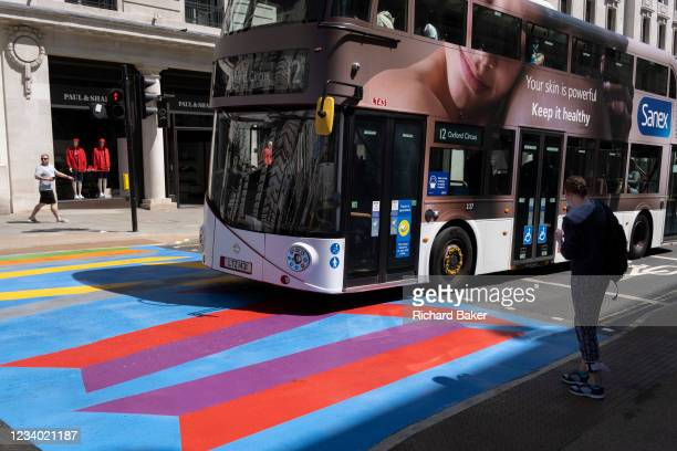 Number 12 bus adorned with an ad for skincare brand Sanex, drives over the multi-coloured markings of a crossing at Lower Regent Street, on 16th July...