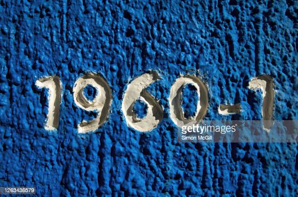 number 1960-1 embossed in a stucco wall painted blue - 1961 stock pictures, royalty-free photos & images