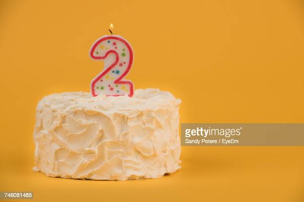 number 2 candle on birthday cake against yellow background - number 2 stock pictures, royalty-free photos & images
