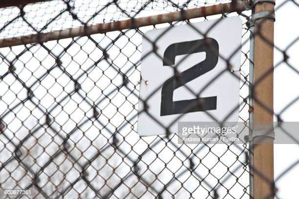 Number 2 Seen Through Chainlink Fence Against Sky