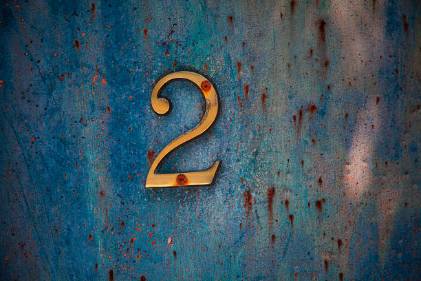 Number 2 sign on an aged painted metal door panel