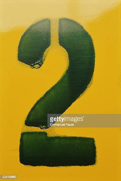 Number '2' stenciled on yellow background, close-up
