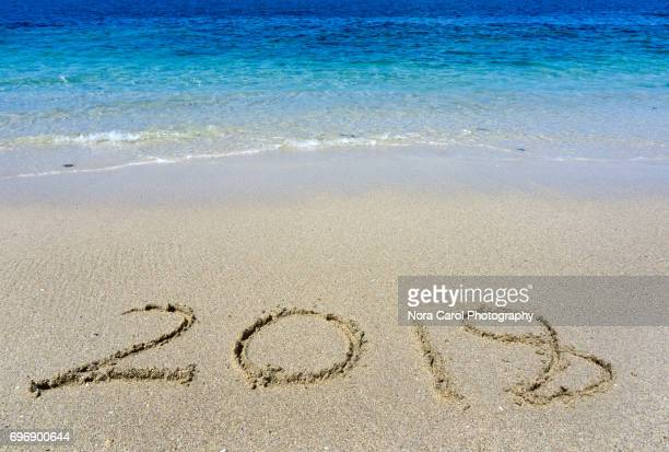 Number 2018 handwritten on a sand beach