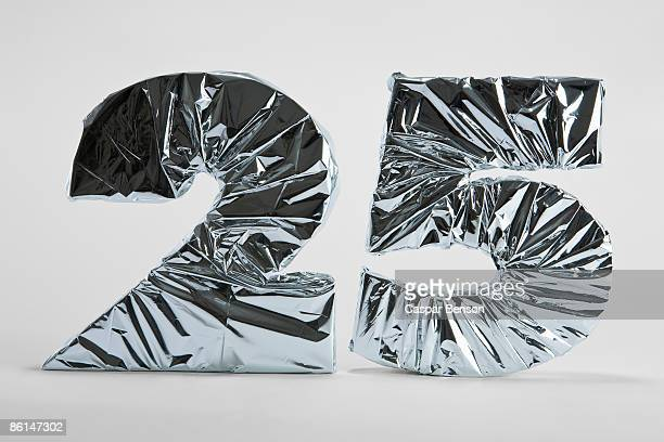 number 25 wrapped in silver foil - jahrestag stock-fotos und bilder