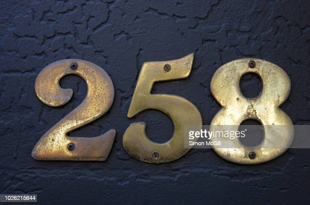 Number 258 in brass numerals on a stucco wall painted dark grey