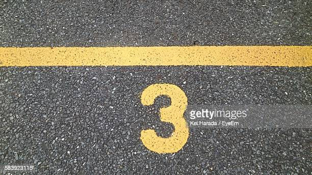 Number 3 And Single Yellow Line On Road