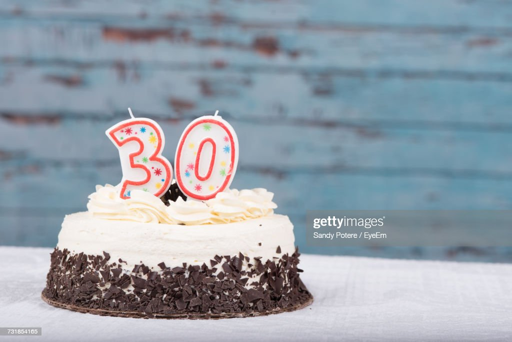 Number 30 Candle On Birthday Cake Over Table Against Wall Stock