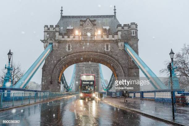 A number 42 double decker bus destination Liverpool Street travels across Tower Bridge during a heavy snow shower on December 10th 2017 Much of the...