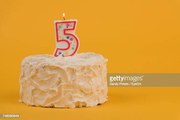 Number 5 Candle On Birthday Cake Against Yellow Background