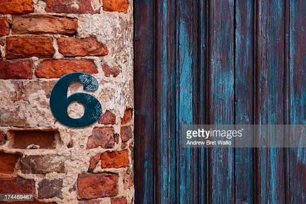 Number 6 sign aginst brickwork close to a doorway