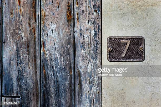 Number 7 metal sign close to an old timber doorway