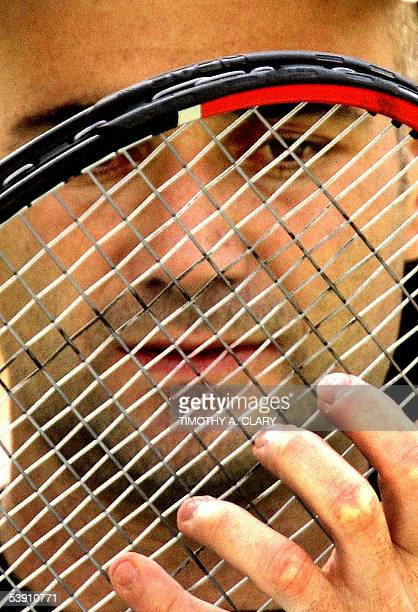 Number 7 seed Andre Agassi of the United States looks through his racket on a break during his match against Ivo Karlovic of Croatia at the 2005 US...