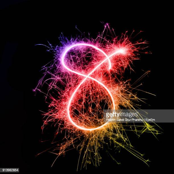 number 8 made by multi colored sparklers at night - number 8 stock pictures, royalty-free photos & images