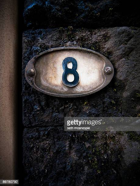 Number eight on a stone wall