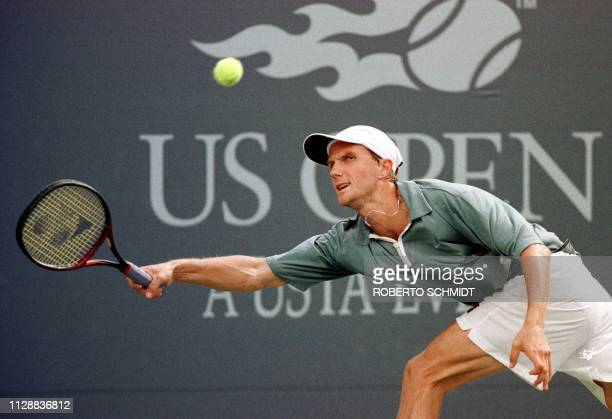 Number nine seed Karol Kucera of Slovakia chases down a return to number eight seed Andre Agassi of the US 08 September at the US Open in Flushing...