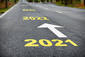 Number of 2021 to 2024 on asphalt road surface with white arrow
