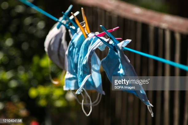 Number of washed face masks hang on a clothesline to dry during coronavirus crisis.