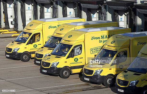 A number of Wm Morrison Supermarkets Plc branded customer delivery vehicle sit during loading at the Ocado Group Plc distribution centre in Dordon UK...