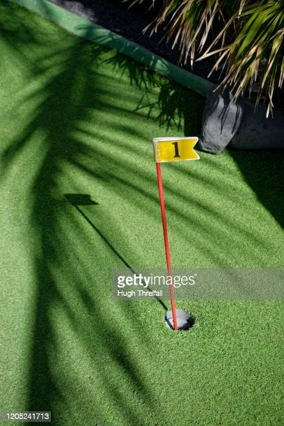 number one flag on a mini golf course. - hugh threlfall stock pictures, royalty-free photos & images